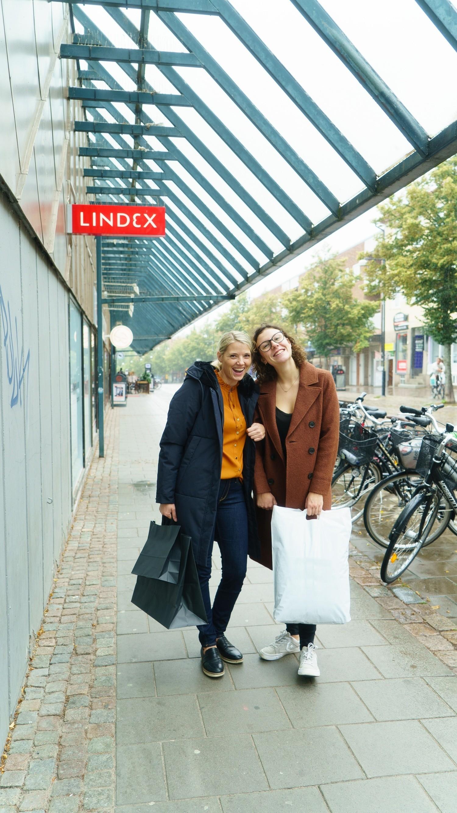 Två kvinnor står utanför galleria med shoppingpåsar i händerna.