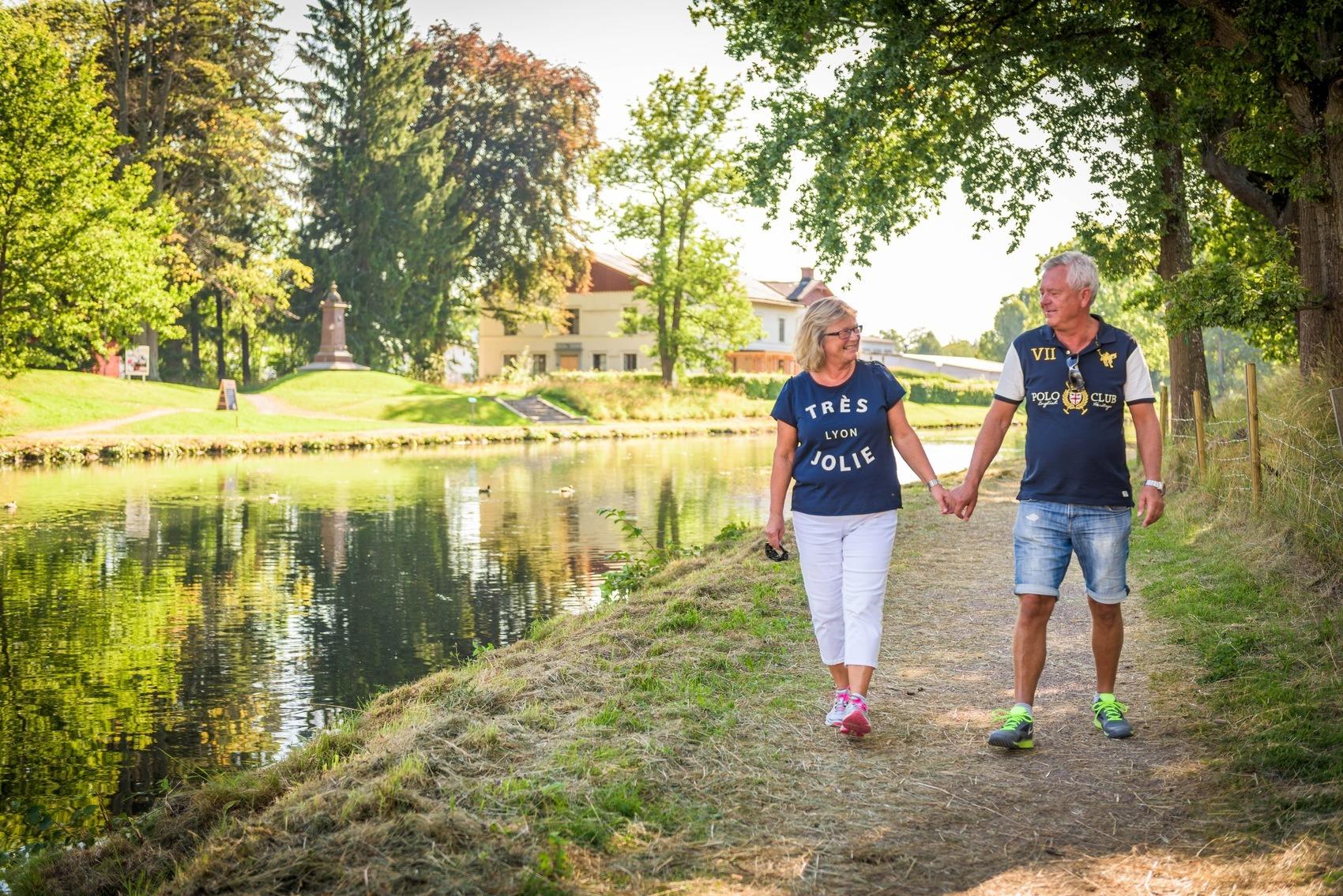 Äldre par går hand i hand längs kanalbanken
