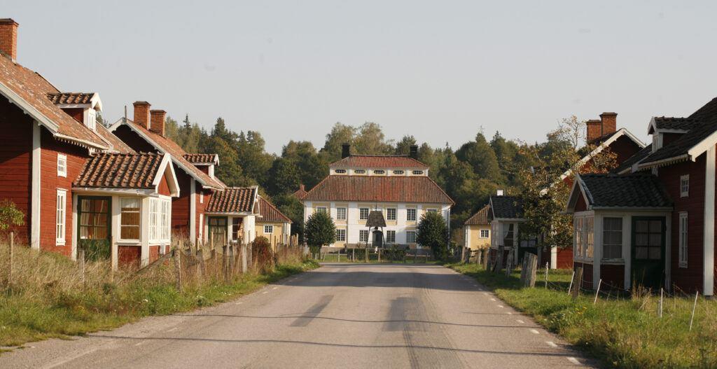 Asfalterad gata med gamla hus. Längst bort ligger en stor vit gård.
