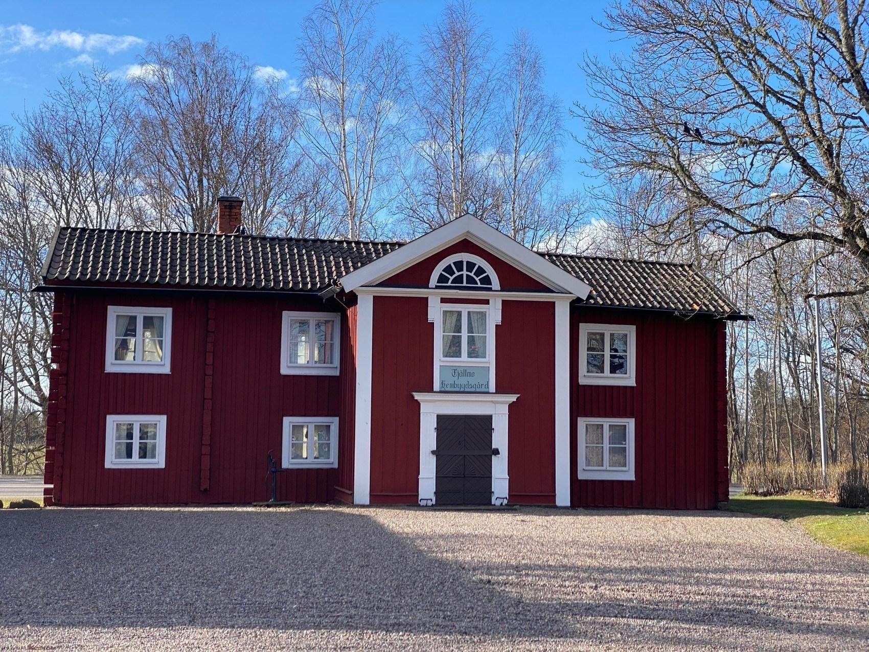 Stor röd gammal träbyggnad med vita knutar.