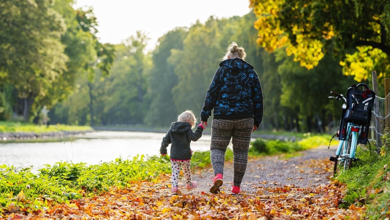 Mamma och barn promenerar längs kanalbanken en höstig dag