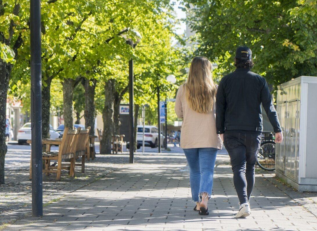 En man och en kvinna promenerar genom centrum