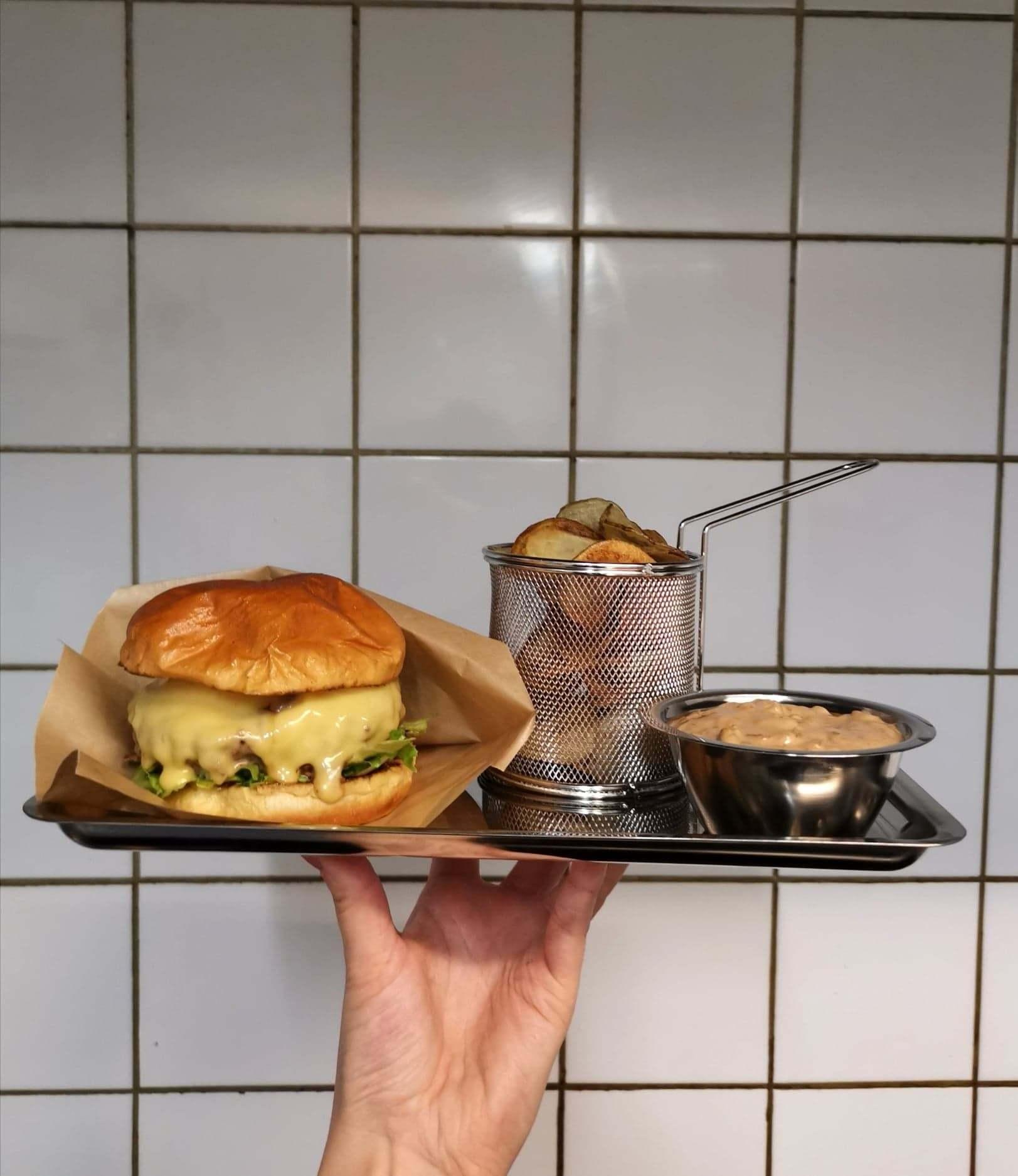 En hand med en bricka med en hamburgermeny