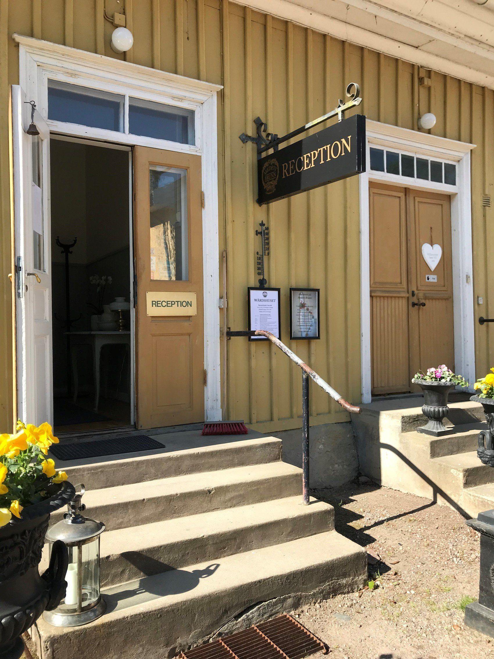 Entréen till Hotell Medevi Brunn. En liten stentrappa leder upp till en öppen dörr i en byggnad med gul träpanel.