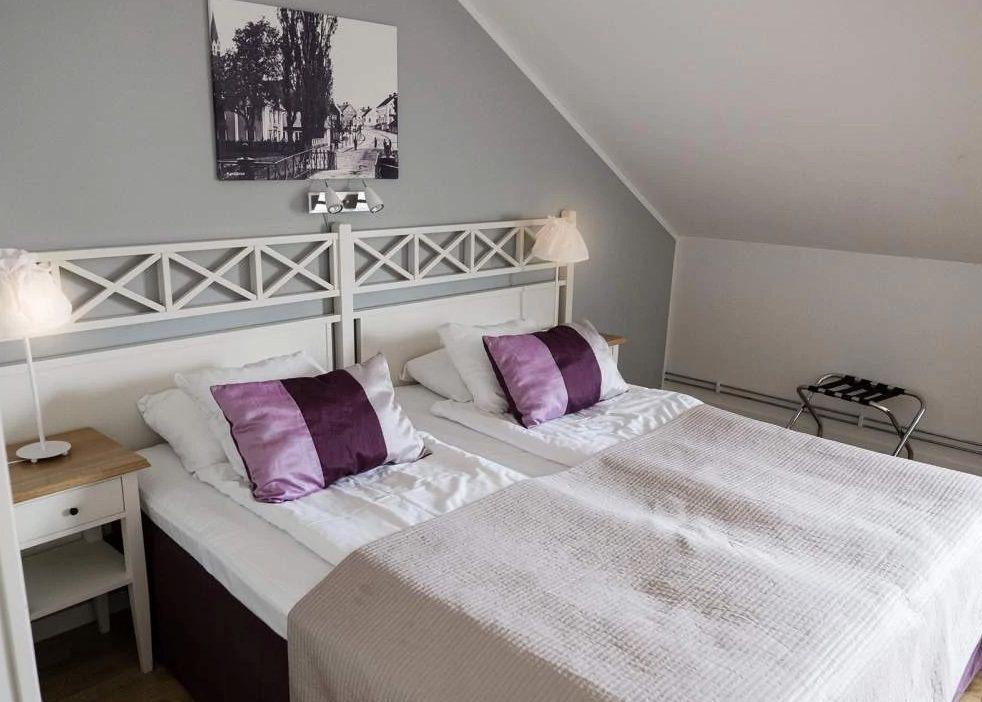 Hotellrum med vit säng. På sängen ligger 2 lila kuddar. Väggen bakom sängen är ljusgrå.