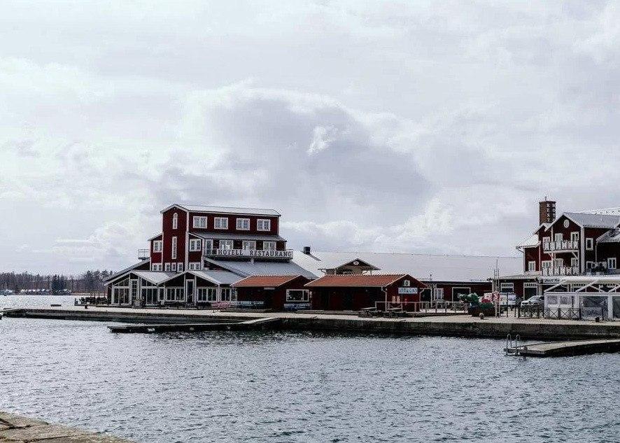 Hög röd träbyggnad ligger ute på en pir i vattnet.