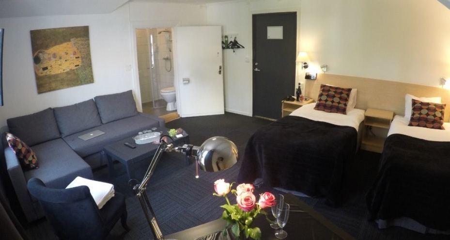 Hotellrum med dubbelsäng och soffa i grått.