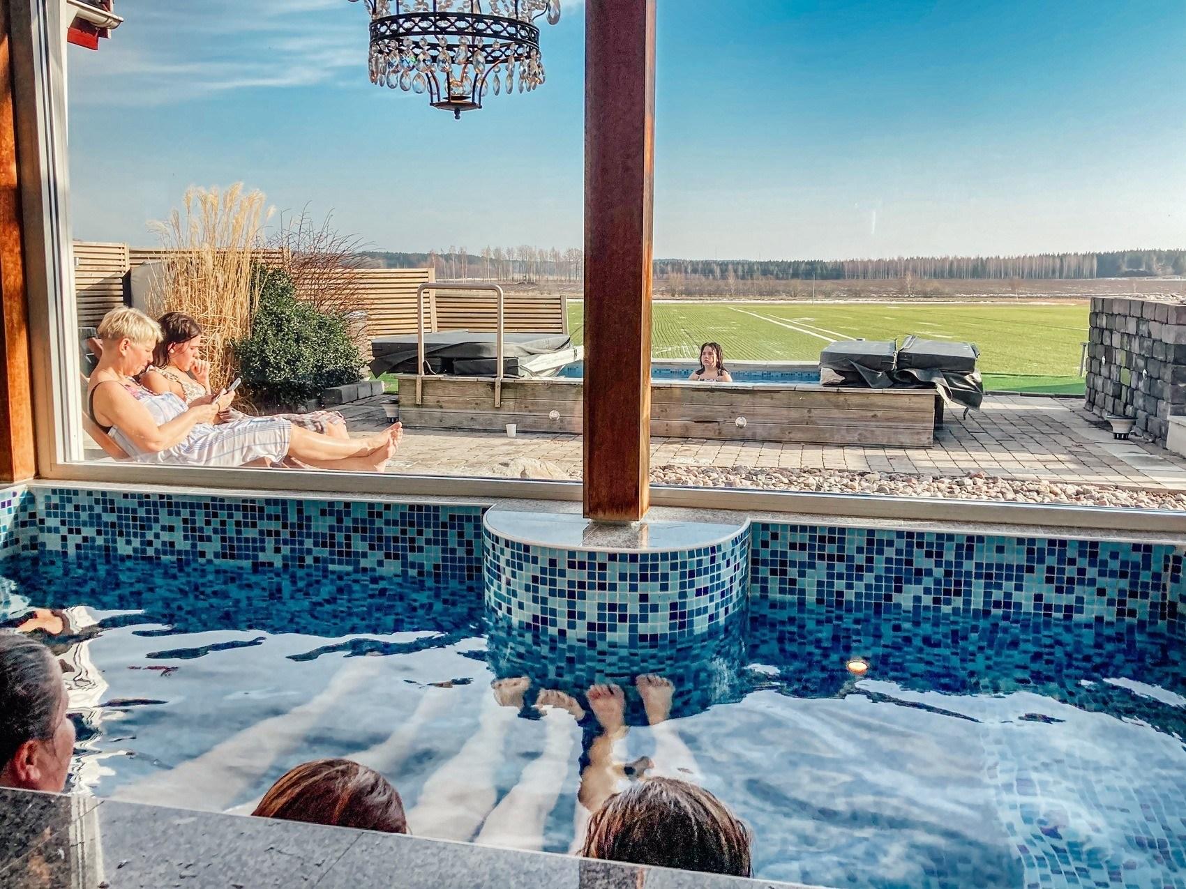 Två personer ligger i en pool med blå mosaik och blickar ut genom två stora fönsterpartier. Utanför ses gröna slätter och blå himmel.