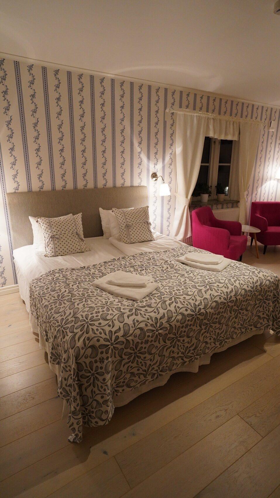 Hotellrum med dubbelsäng och 2 röda fåtöljer.