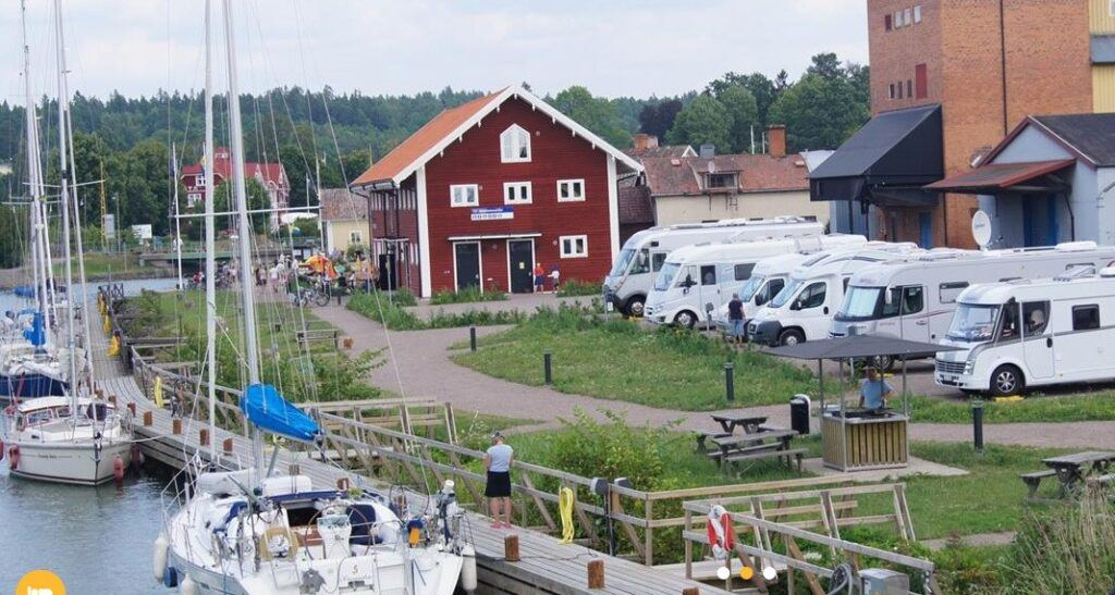 Foto taget uppifrån på hamnområde. I vattnet ligger stora segelbåtar. På land står husbilar parkerade på rad.