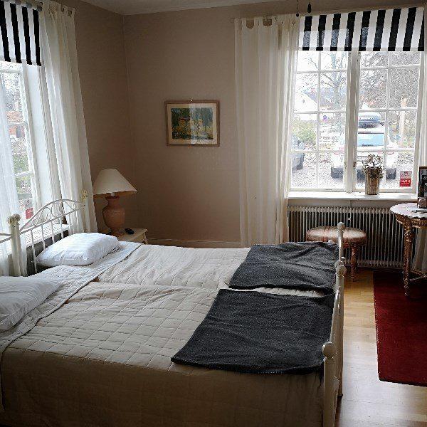 Rum Rex Bed and breakfast med dubbelsäng och randiga gardiner.