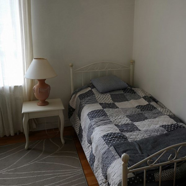Rum med enkelsäng. Bredvid sängen står en lampa på ett bord.