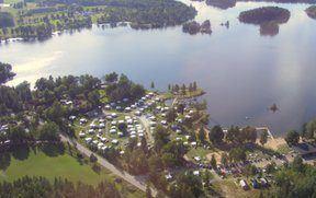 Flygfoto över camping som ligger precis intill skogsjö.
