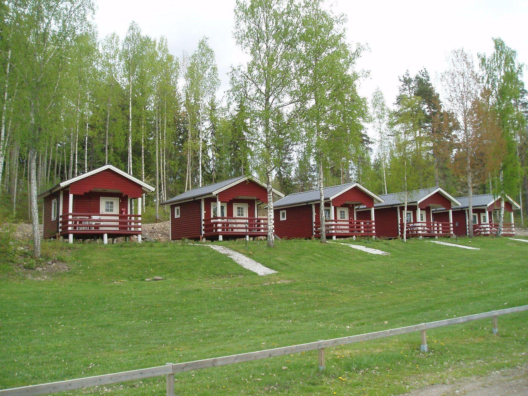Röda campingstugor ligger på rad på en lite upphöjd gräsplan.