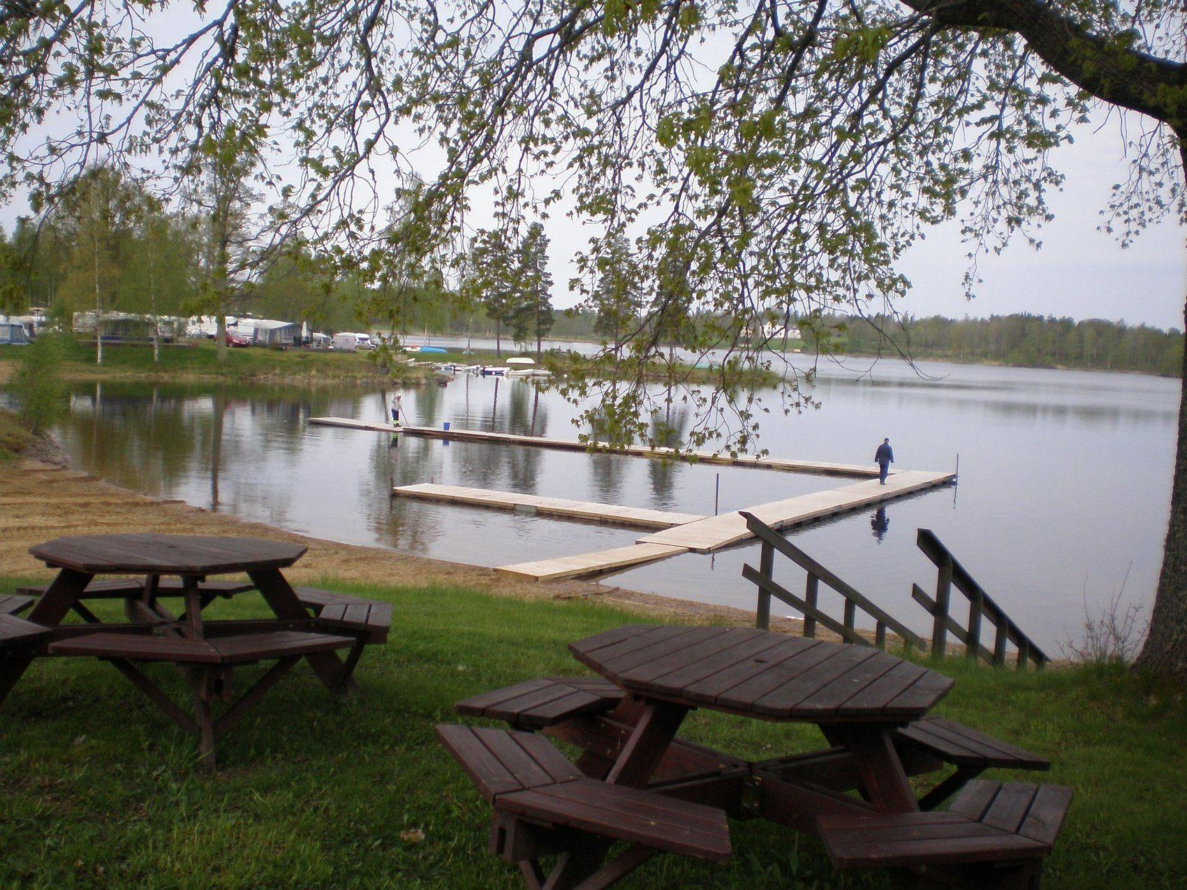 Badplats med gräsplan och bryggor ut i vattnet.