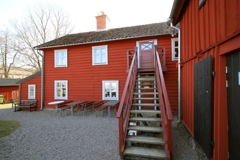 Röda gamla trähus. Rakt fram finns en trapp som leder upp till en dörr på ovanvåningen på ett av husen.