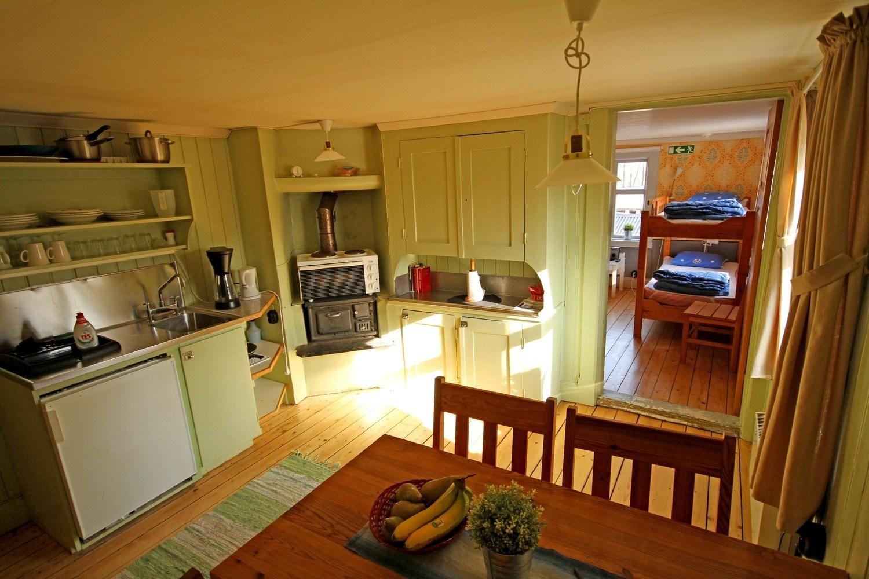 En gammal arbetarbostad invändigt. På bilden syns ett kök med köksbord.