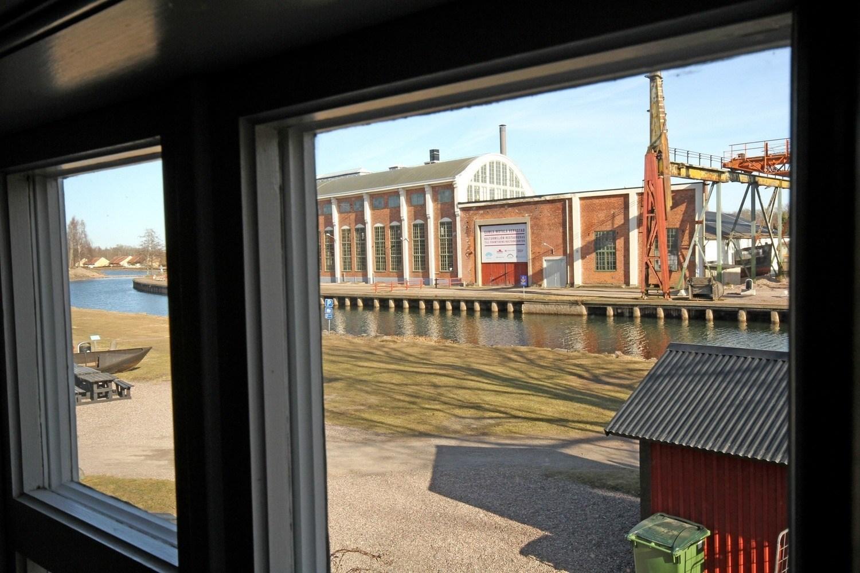 Foto taget genom ett fönster. Utanför fönstret syns en stor gammal fabriksbyggnad och framför rinner en kanal.