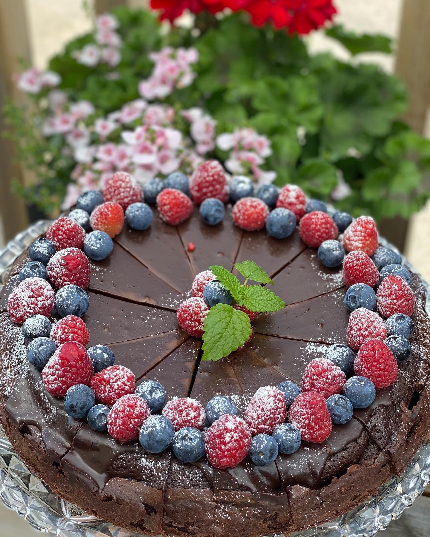 En chokladkaka med blåbär och hallon