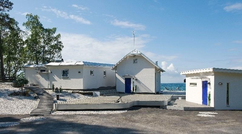 Vitt hus med blåa detaljer. I bakgrunden syns Varamons vatten.