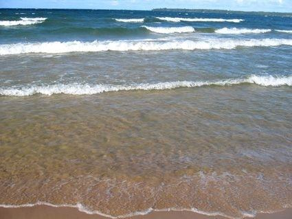 Vågor slår in mot en sandstrand.