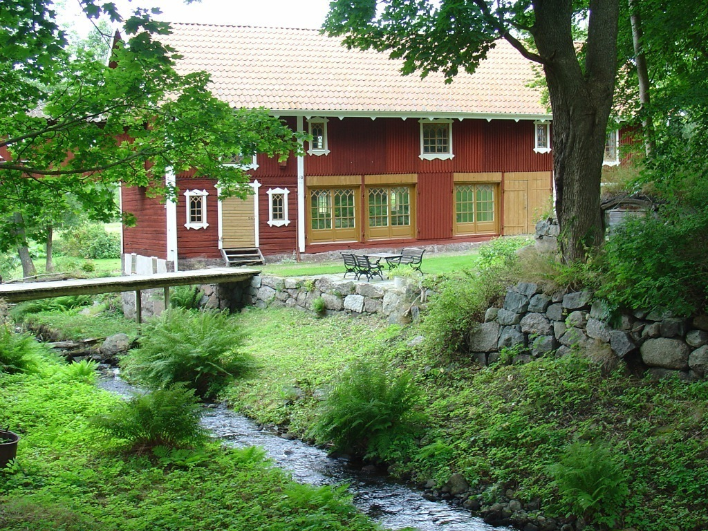 Stor röd laduliknande byggnad omgiven av grön växtlighet.