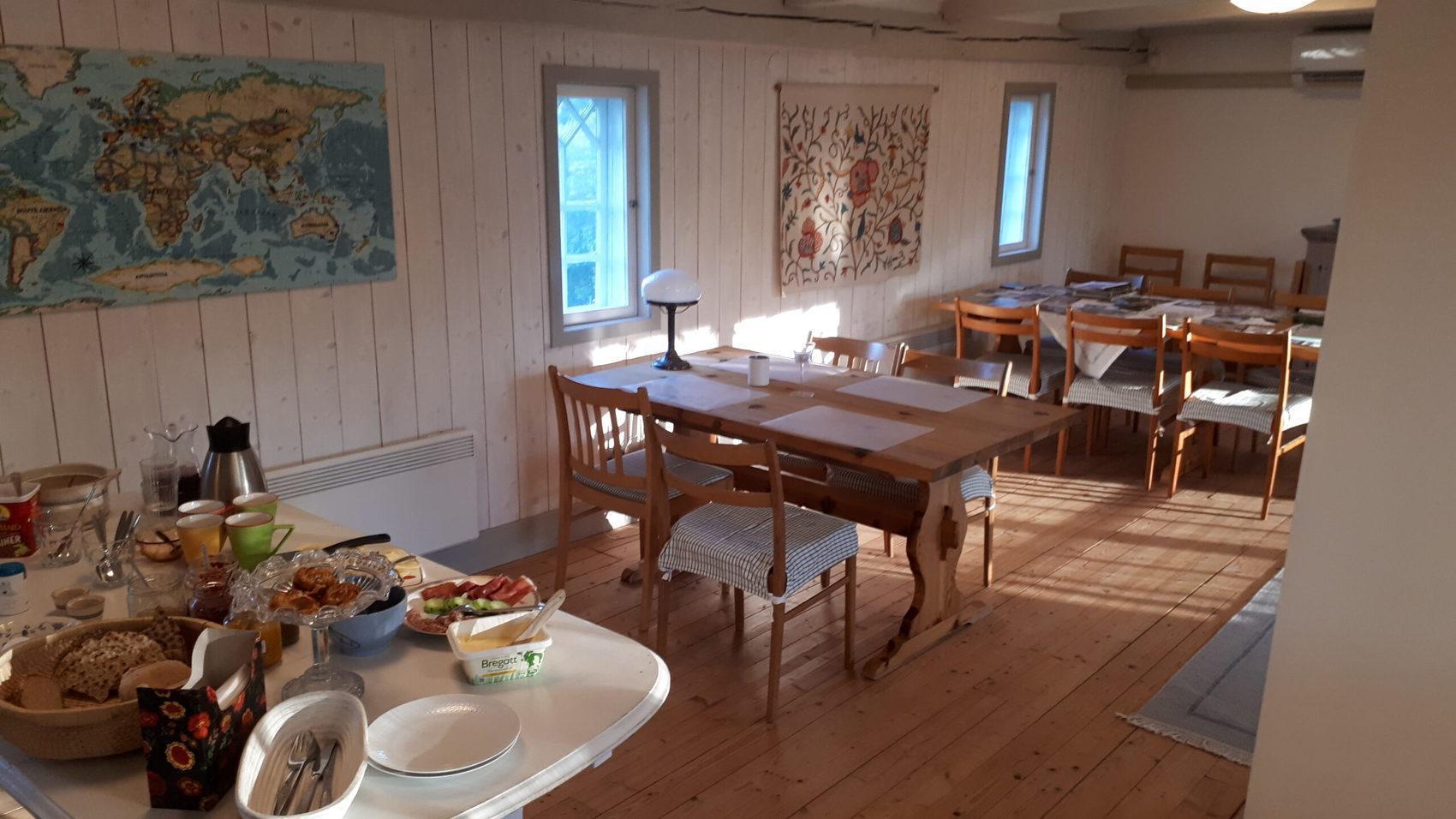 Matsal med bord och stolar. I förgrunden står en frukostbuffé uppdukad.