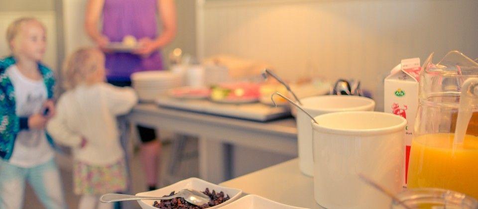 Framdukad frukostbuffé. I bakgrunden syns två barn som plockar frukost med en vuxen.