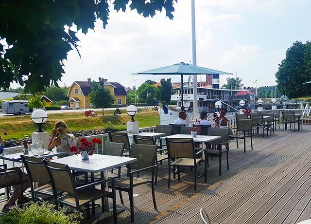 Uteservering med bord, stolar och parasoll