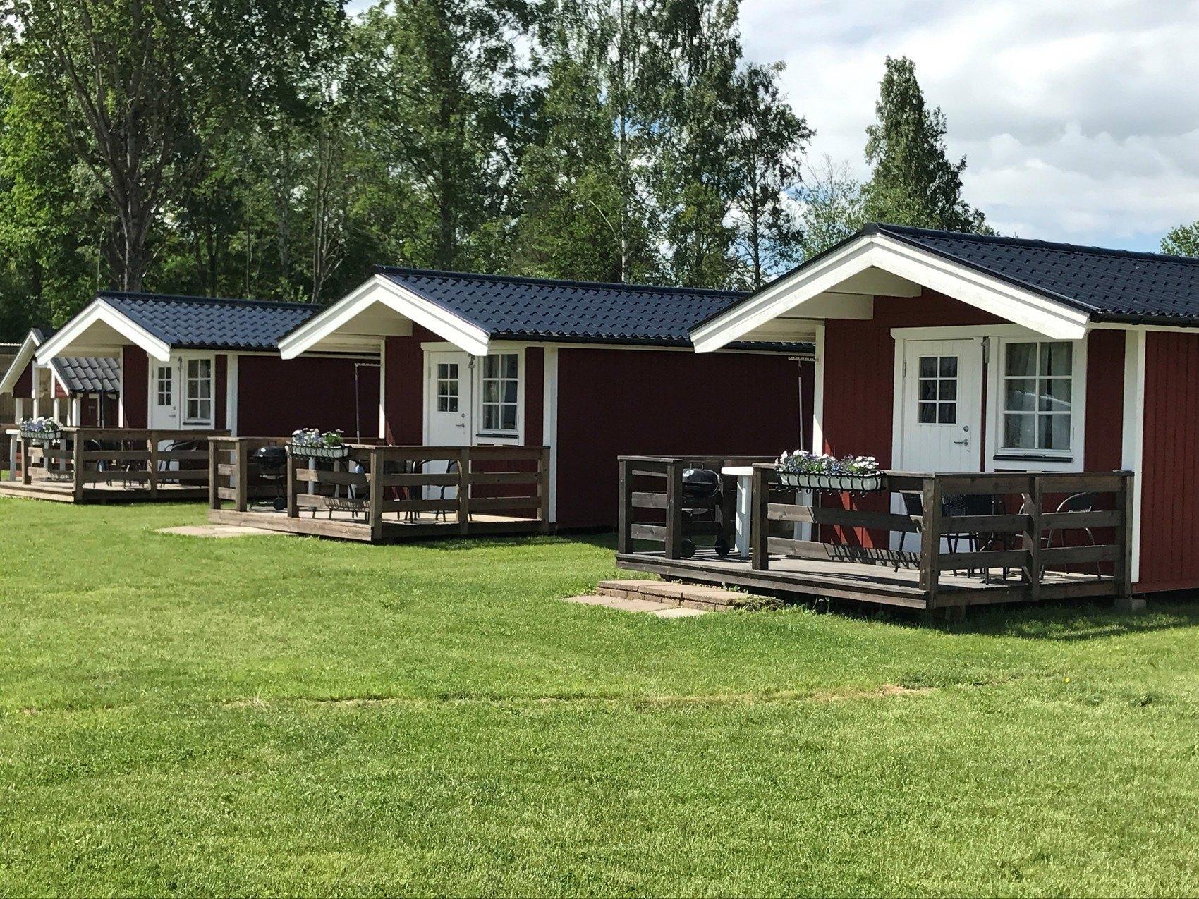 Tre röda campingstugor ligger på rad på en gräsplan.