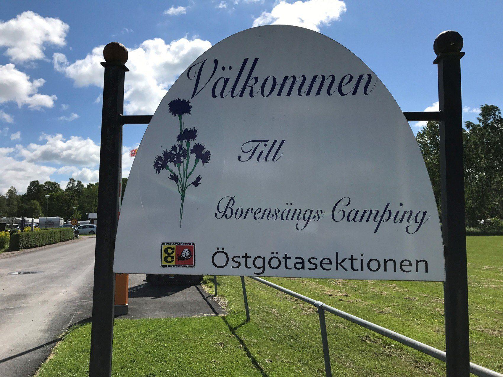 En vit skylt med texten Välkommen till Borensängs camping. Bredvid texten finns en illustrerad blåklint.