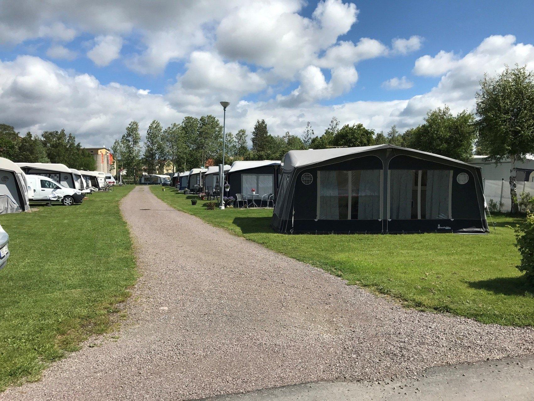 Väg genom campingområde. Längst fram syns en husvagn med ett stort förtält och i bakgrunden skymtar fler.