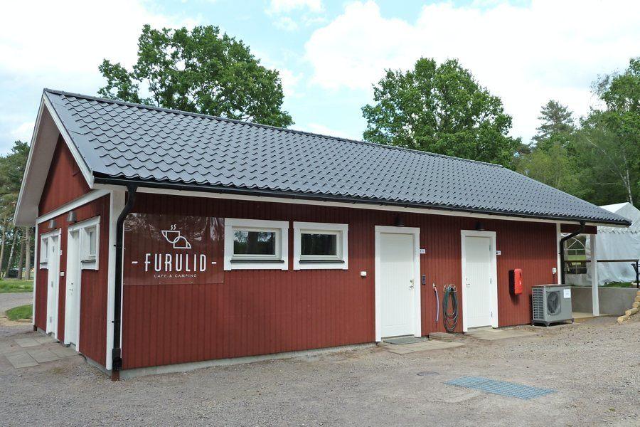 Röd byggnad med två vita dörrar. På husväggen står det Furulid.