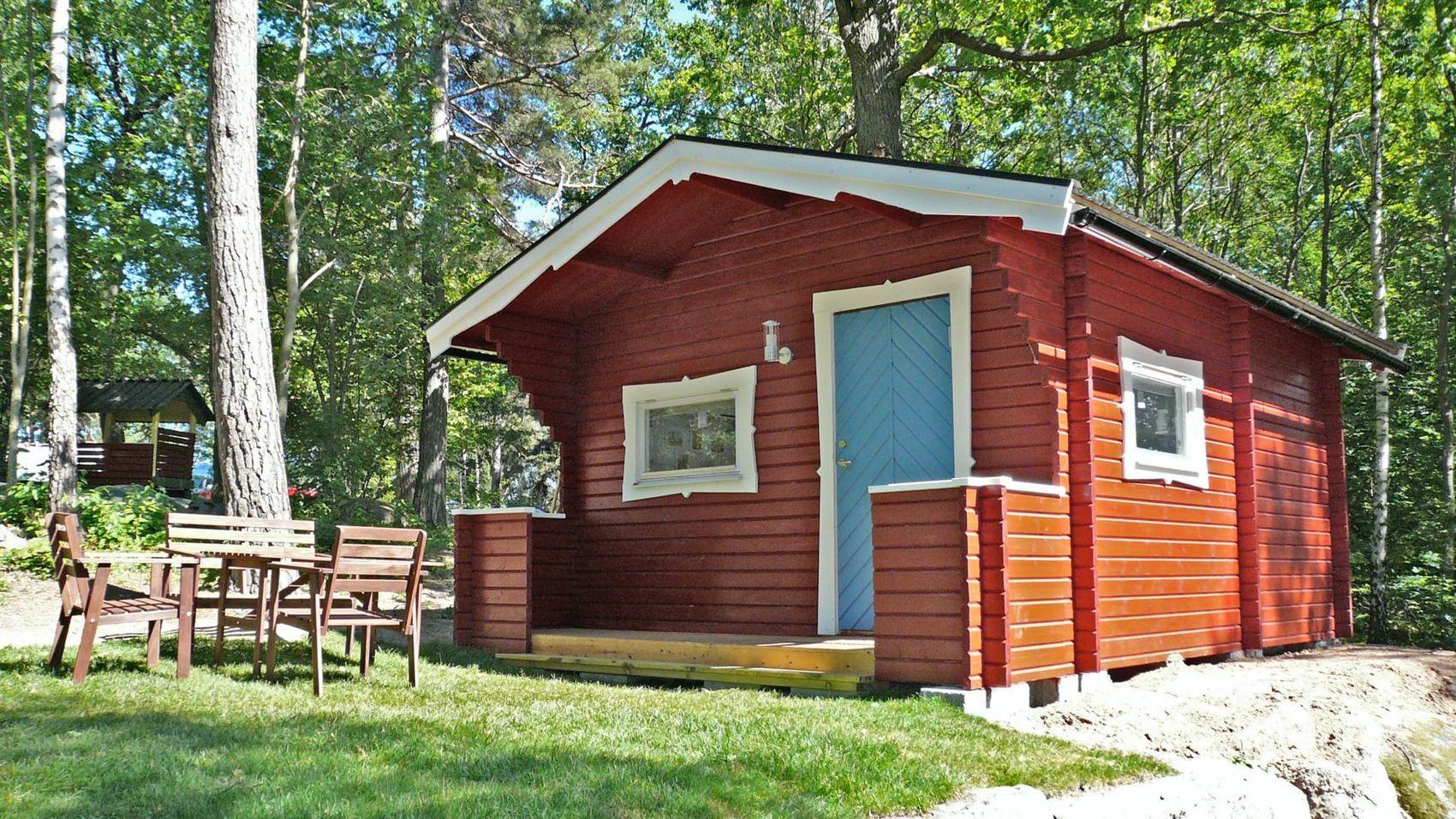 Röd campingstuga med blå dörr.