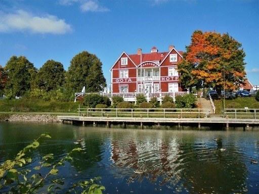 En vacker gammal röd byggnad omgiven av träd i höstiga färger. Framför byggnaden rinner en kanal.