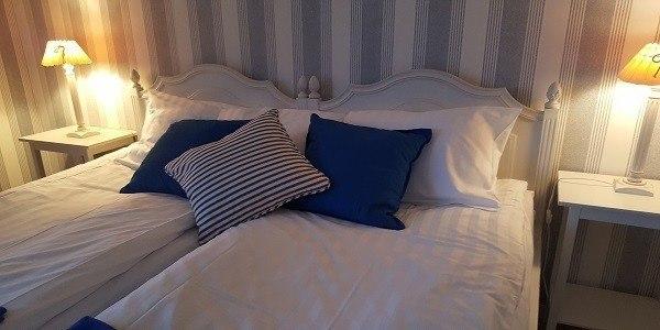 Hotellrum med säng. Detaljerna går i vitt och blått. Väggen har en tapet med vita och blå lodräta linjer.