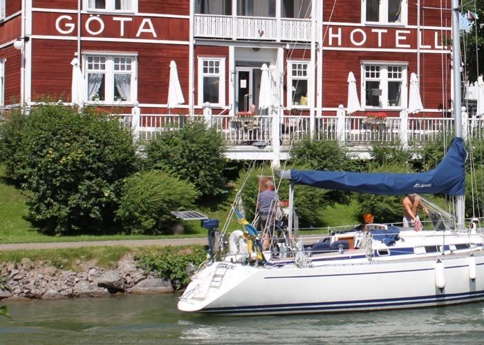 En stor vit segelbåt passerar Göta Hotell längs med Göta Kanal.