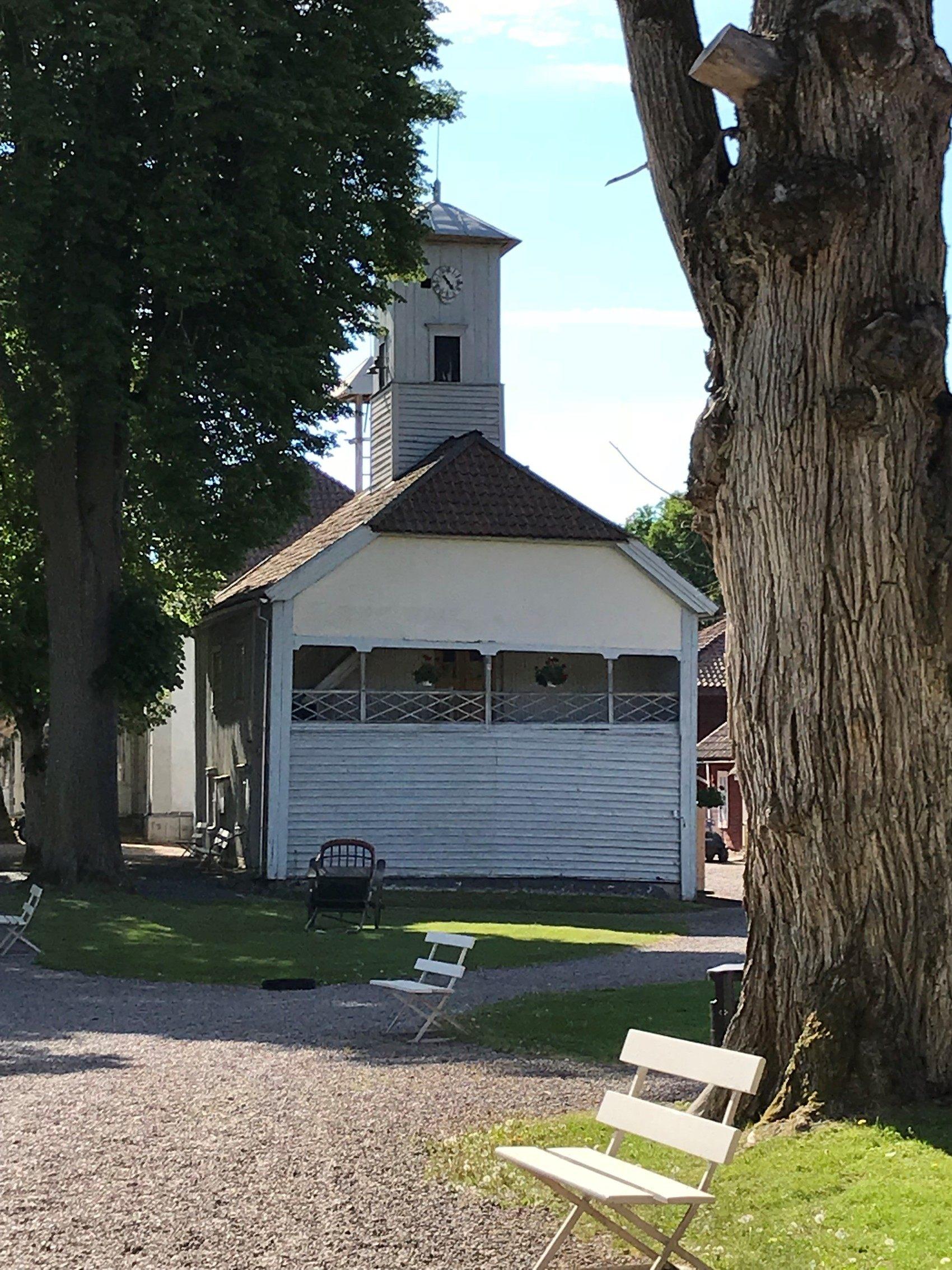 Gammal vit träbyggnad med klocktorn