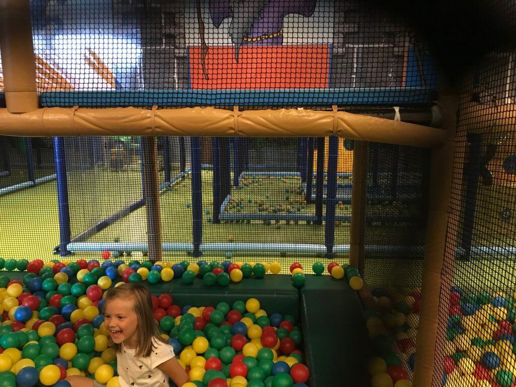 Flicka leker i ett hav av färglada bollar