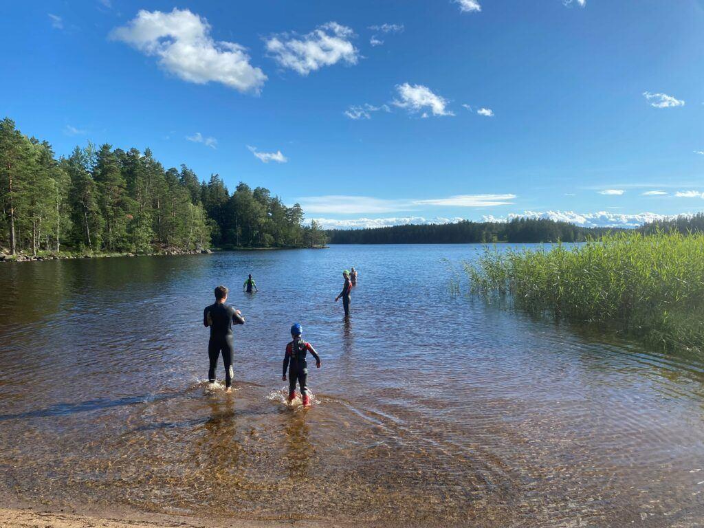 Familj i våtdräkt kliver i vattnet i en lite skogsjö