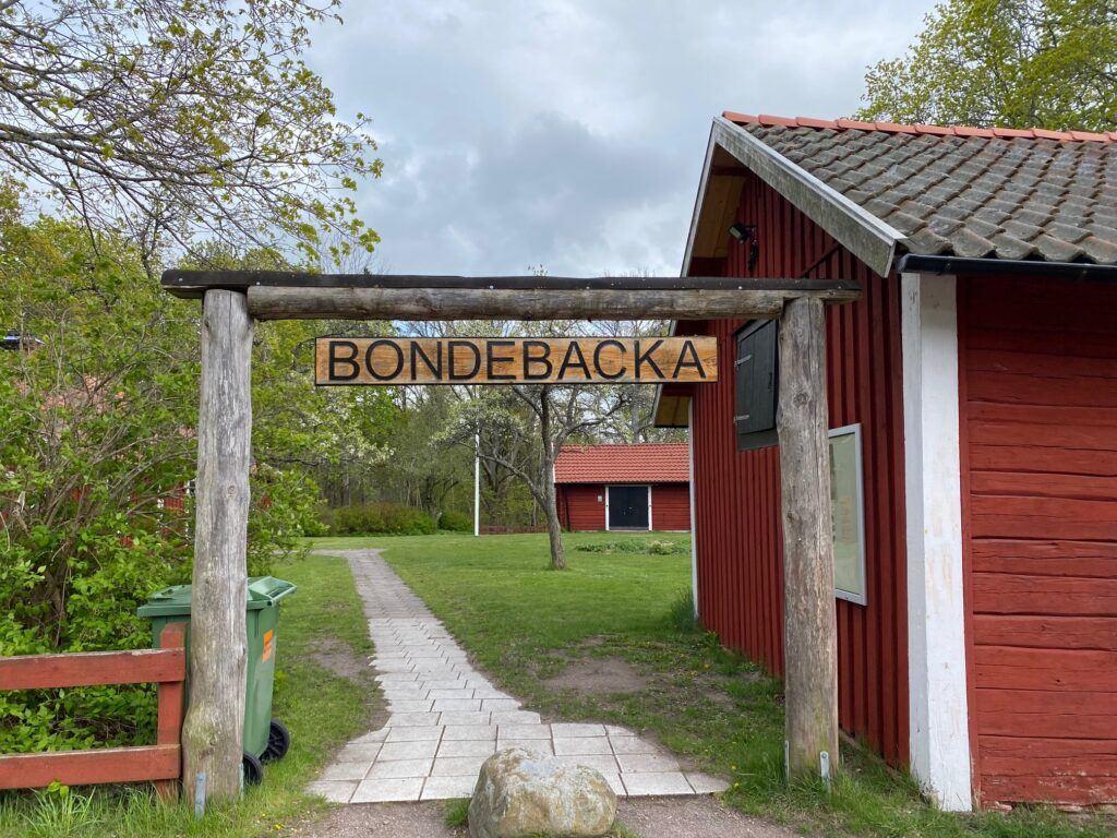 Skylt i trä med texten Bondebacka hänger över ingång till gård med röda hus.