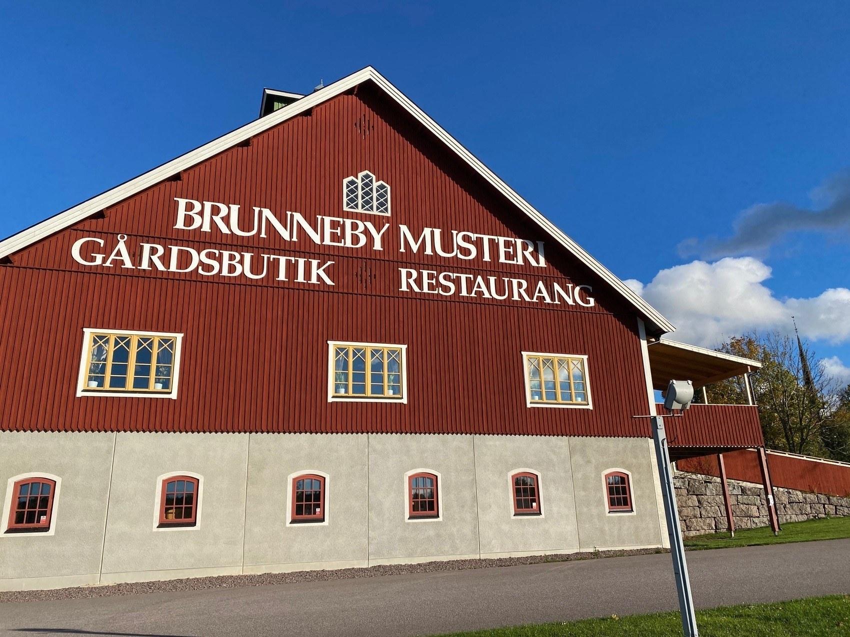 Stor röd lada med texten Brunneby Musteri på gaveln.