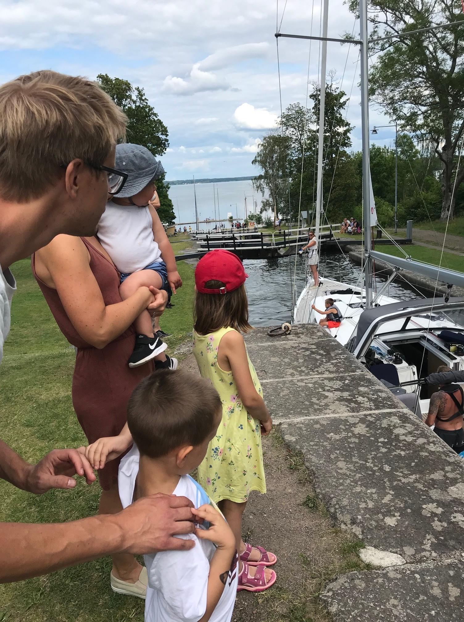 Familj med två vuxna och 3 barn står och tittar på en segelbåt som slussas i Göta Kanal.
