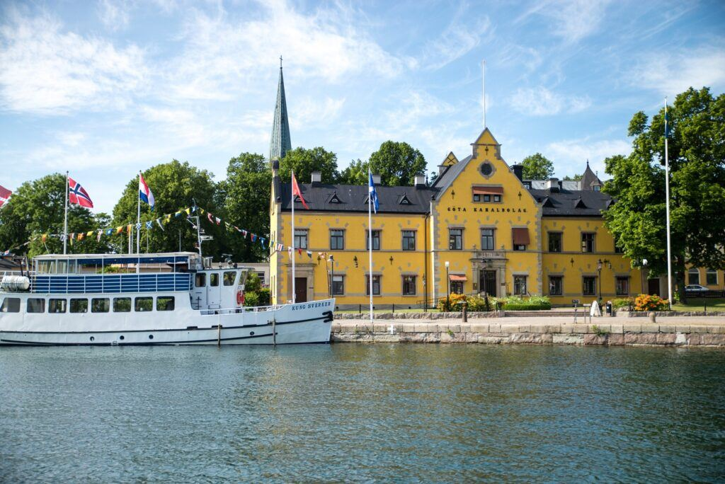 Stor vita passagerarbåt passerat stort gult stenhus.