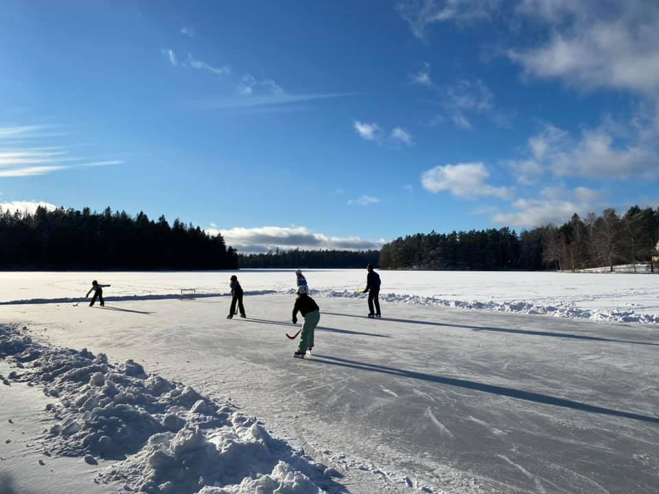 Barn spelar hockey på en frusen sjö.
