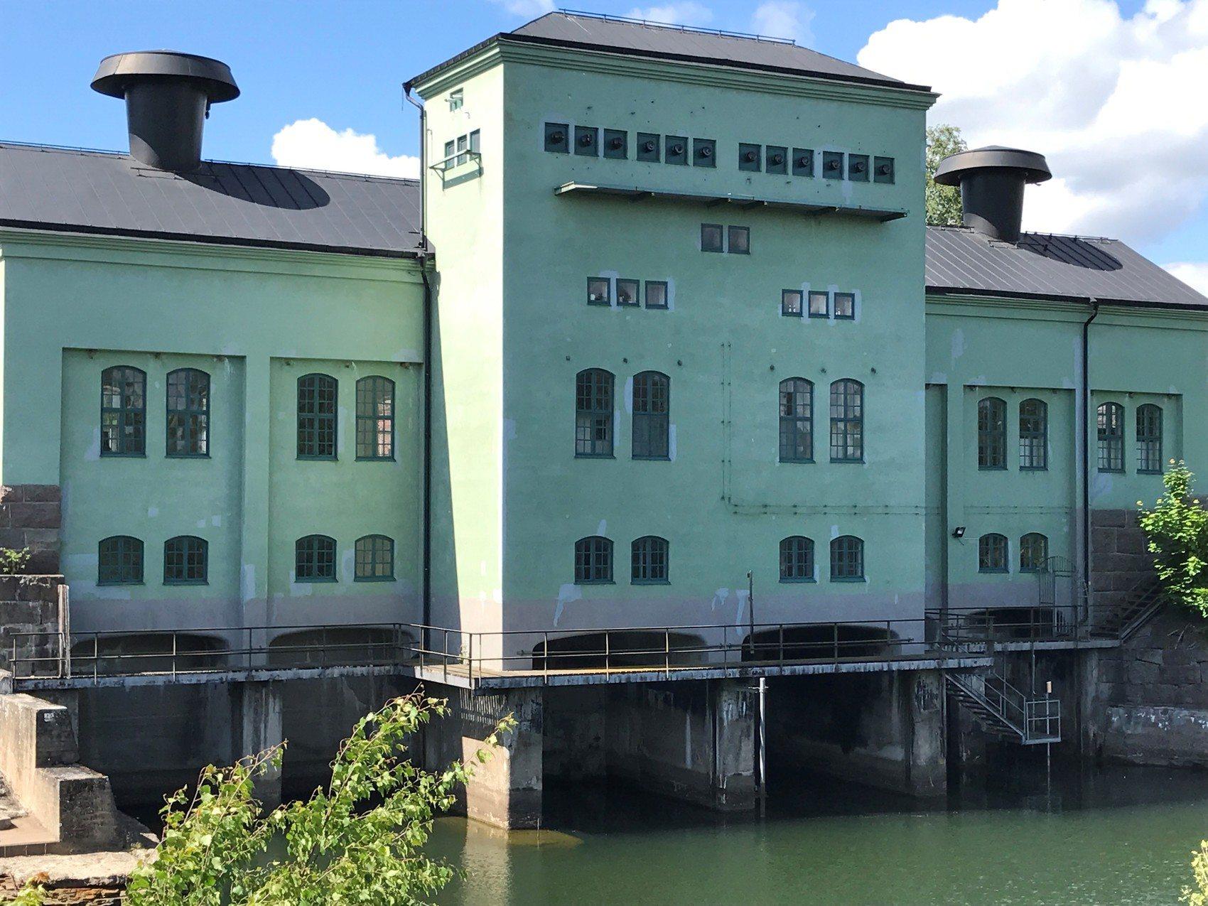 Stor gammal ljusgrön fabriksbyggnad som delvis är byggd i vatten.