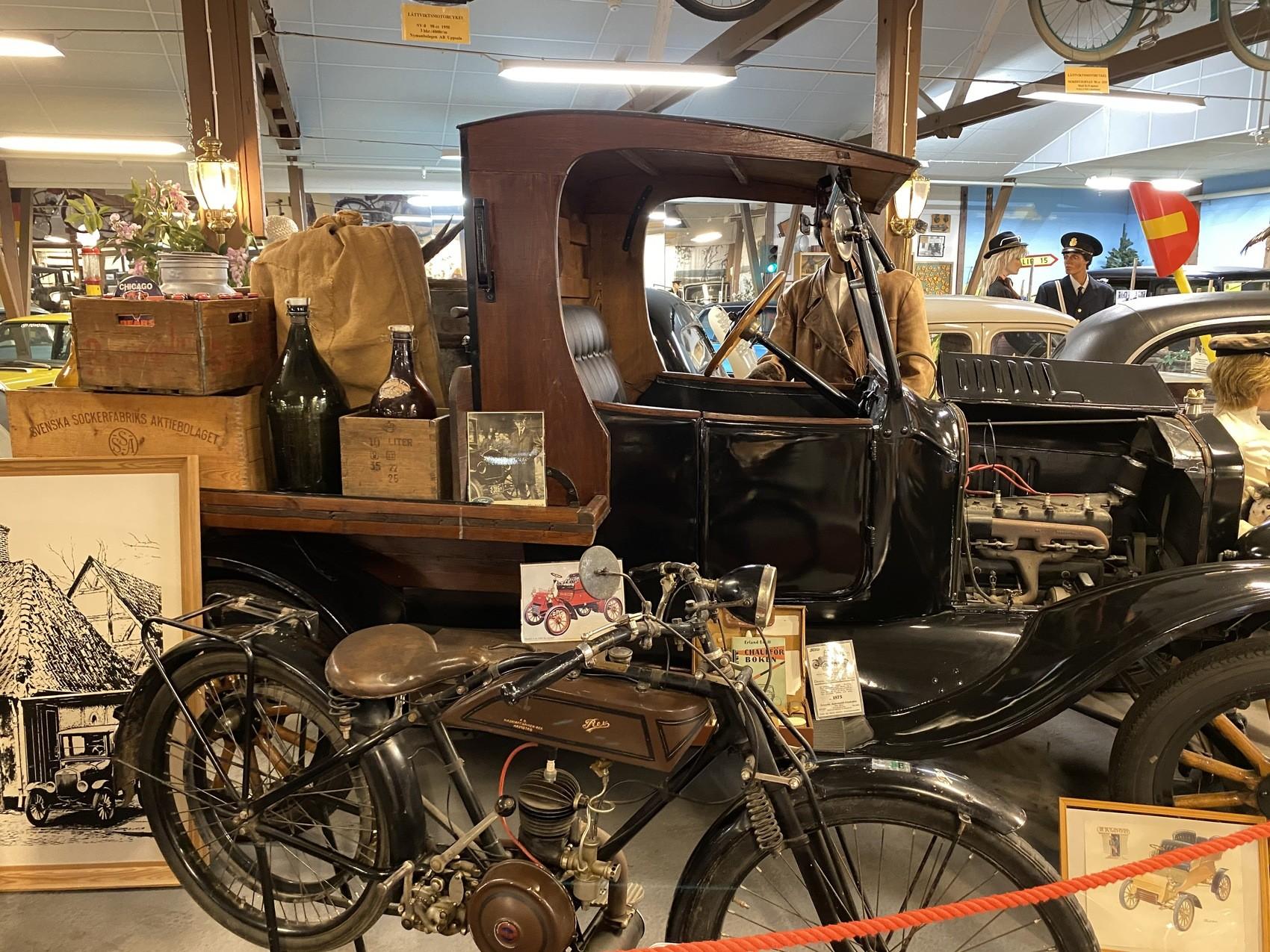 En mycket gammal moped står framför en väldigt vacker glänsande gammal bil.