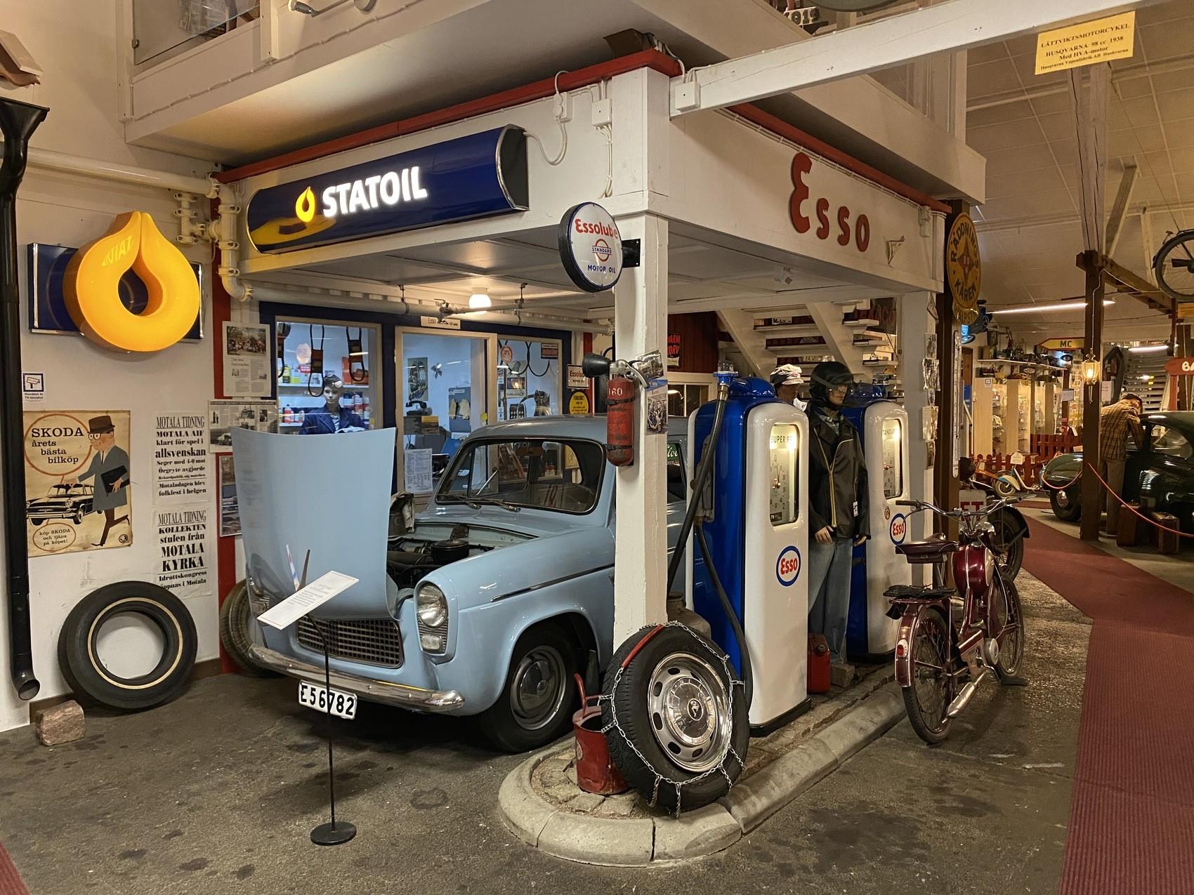 En gammal mack som det står ESSO på, i den står en gammal blå bil med motorhuven öppen. En gammal moped står lutad mot macken.
