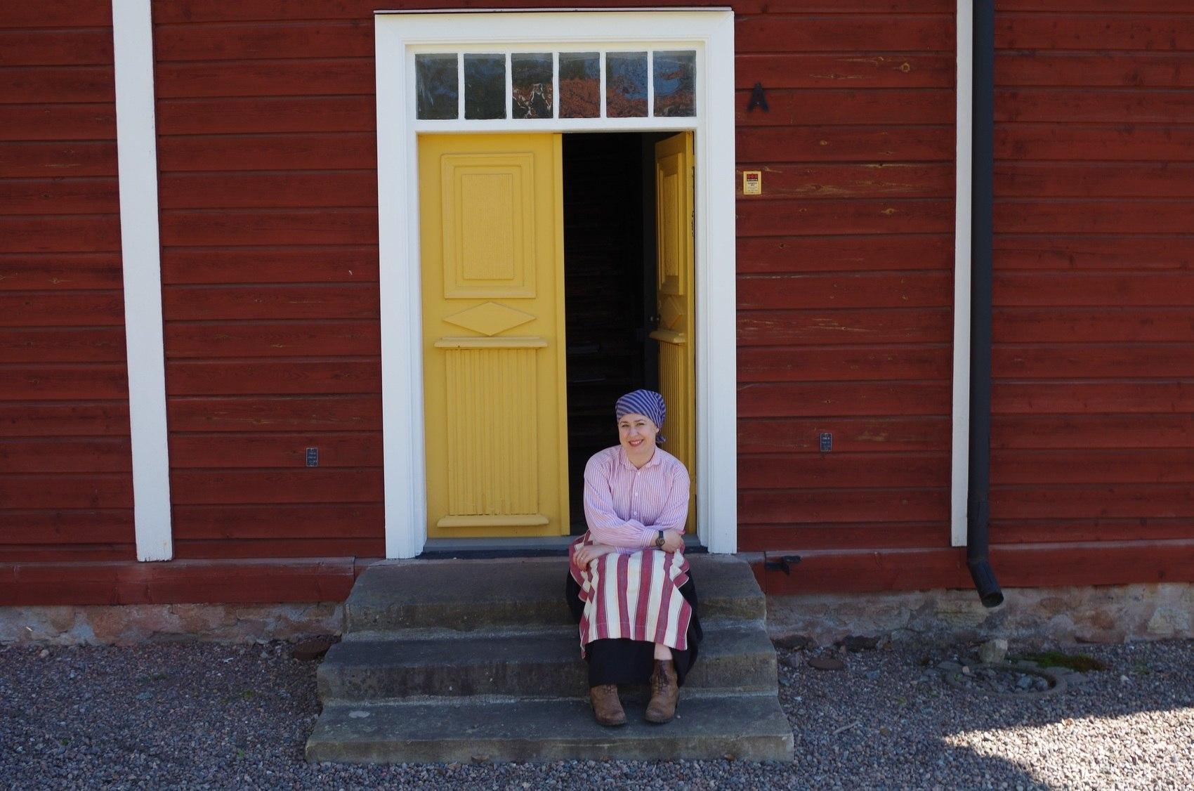 Kvinna i gamla kläder sitter på en trappa utanför röd träbyggnad.