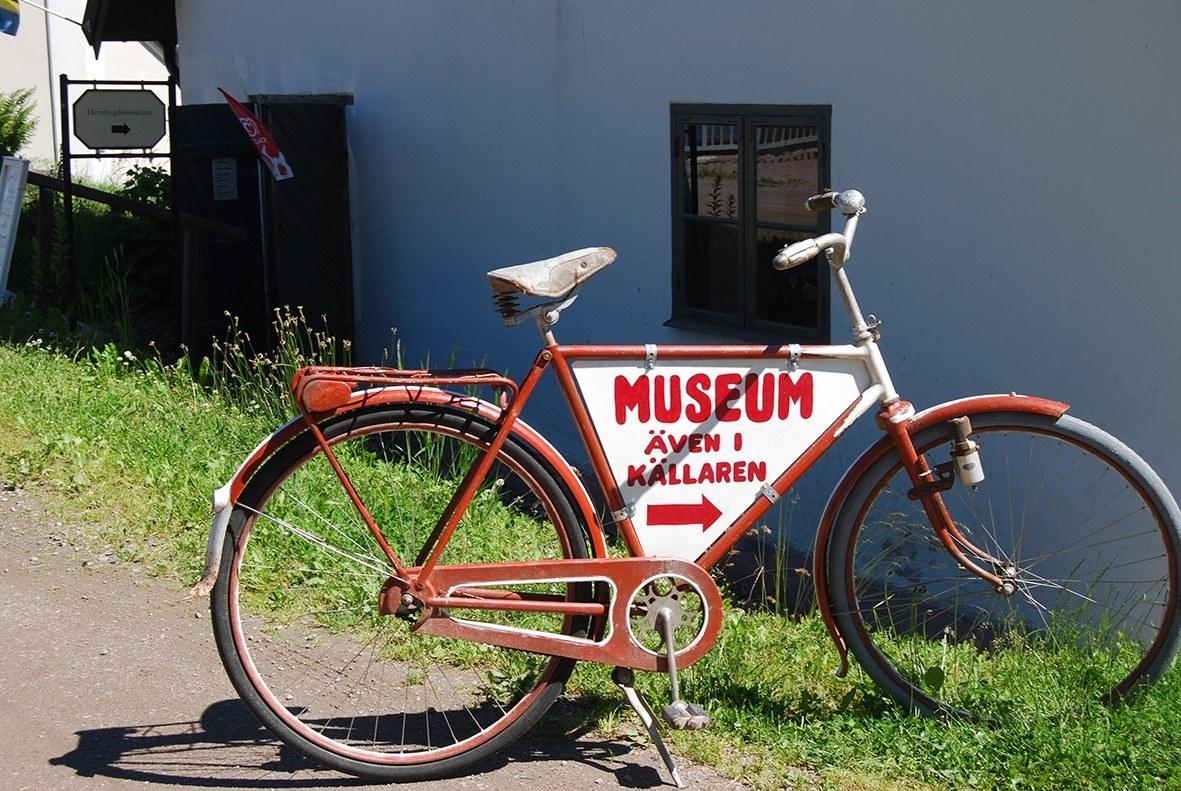 """Röd cykel med skylt hängandes på ramen med texten """"Museum"""""""